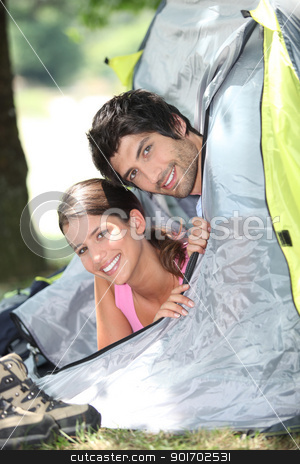 Young couple sticking their heads out of a tent door stock photo, Young couple sticking their heads out of a tent door by photography33