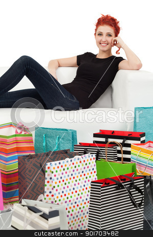 Young female and shopping bags stock photo, A happy shopping girl sitting on a white couch surrounded with shopping bags.  by © Ron Sumners