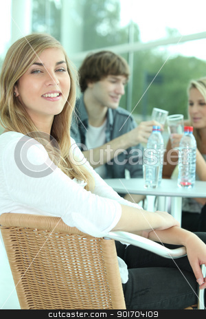 Three young people drinking water in a cafeteria. stock photo, Three young people drinking water in a cafeteria. by photography33