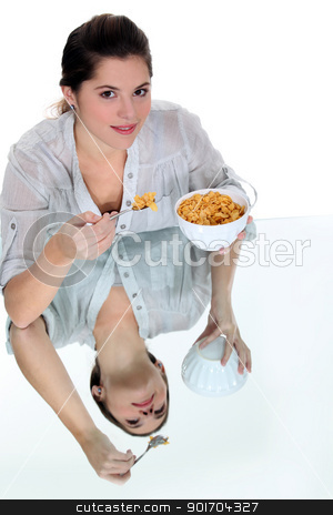 Woman eating bowl of cereal stock photo, Woman eating bowl of cereal by photography33