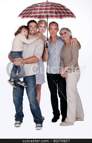Family standing under umbrella stock photo, Family standing under umbrella by photography33