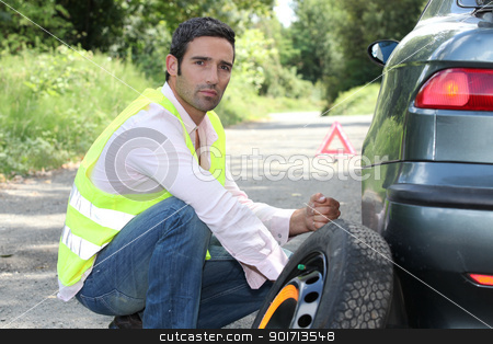 Man changing a tyre at the side of the road stock photo, Man changing a tyre at the side of the road by photography33