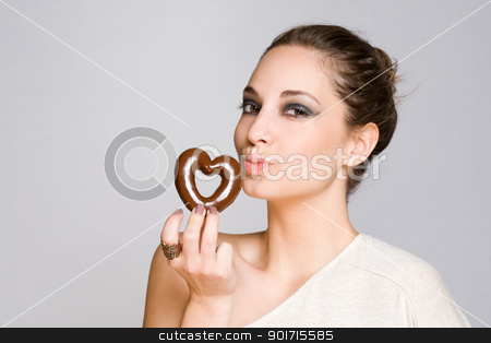Attractive young brunette with chocolate heart. stock photo, Portrait of an attractive young brunette with shiny chocolate heart. by exvivo