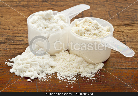 whey protein powder - two scoops stock photo, two measuring scoops of whey protein powder - isolate (white) and concentrate (creamy) by Marek Uliasz
