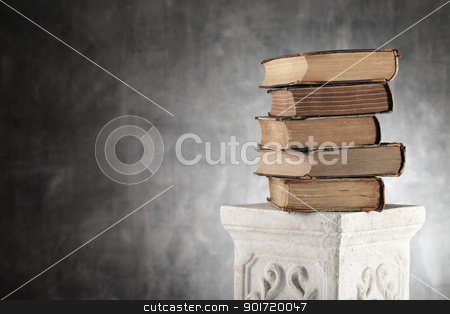 Old Knowledge stock photo, Stack of antique yellowed books on a plaster column. by Stocksnapper