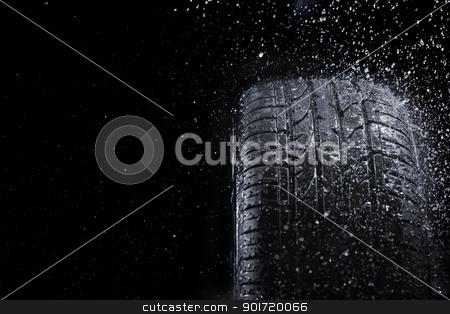 Rain Tire stock photo, New car tire in rain. by Stocksnapper