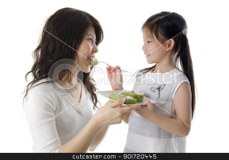 Feeding cake for mama stock photo, Little Asian girl feeding cake for her mother by szefei