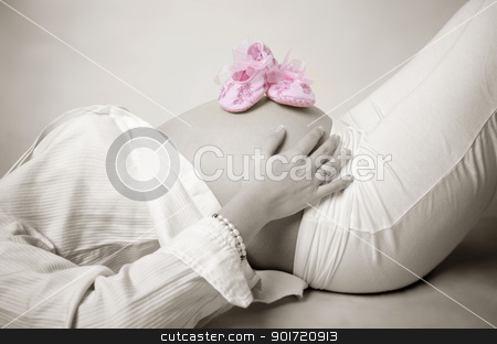 Pink shoes stock photo, Pink shoes on mummy stomach by szefei