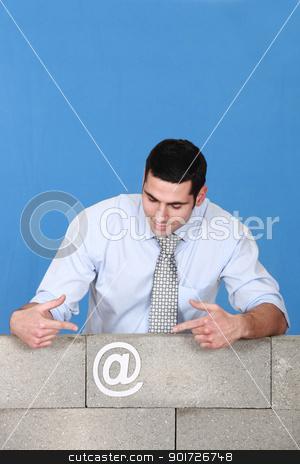 Man pointing towards at symbol stuck to wall stock photo, Man pointing towards at symbol stuck to wall by photography33