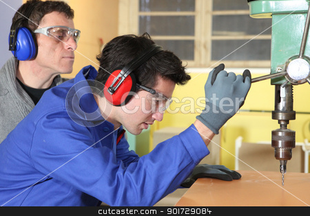 Young man using a bench drill stock photo, Young man using a bench drill by photography33