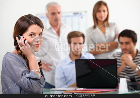 Young woman on the phone with colleagues gathered round a laptop stock photo, Young woman on the phone with colleagues gathered round a laptop by photography33