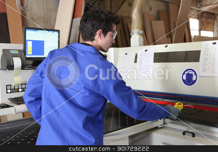 Young worker operating factory machine stock photo, Young worker operating factory machine by photography33