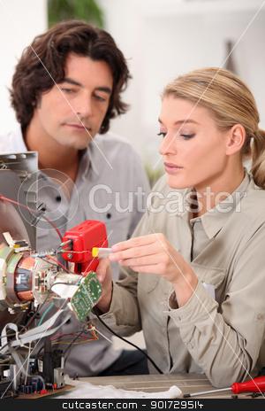 Woman repairing a television set stock photo, Woman repairing a television set by photography33