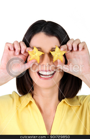 Woman holding slices of starfruit in front of her eyes stock photo, Woman holding slices of starfruit in front of her eyes by photography33