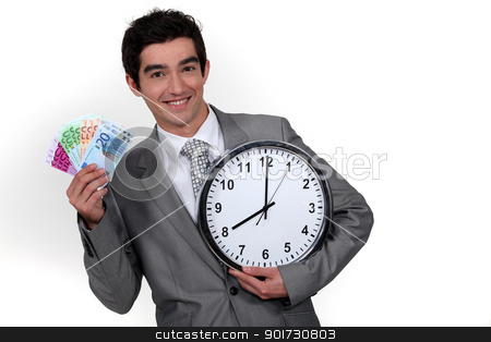 Young businessman with a wad of cash by 8 o'clock stock photo, Young businessman with a wad of cash by 8 o'clock by photography33
