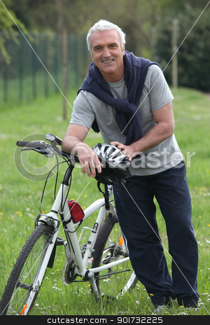 Cyclist stopped in a park stock photo, Cyclist stopped in a park by photography33