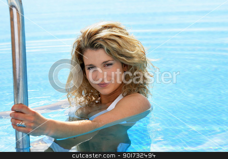 Woman on the steps of a swimming pool stock photo, Woman on the steps of a swimming pool by photography33
