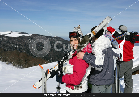 Group of young skiers standing atop a mountain stock photo, Group of young skiers standing atop a mountain by photography33