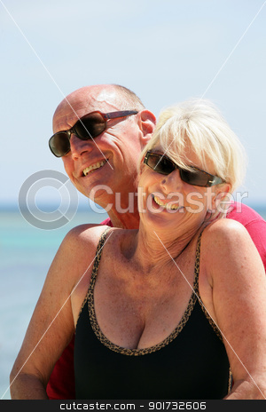 Senior couple stood on a secluded beach stock photo, Senior couple stood on a secluded beach by photography33