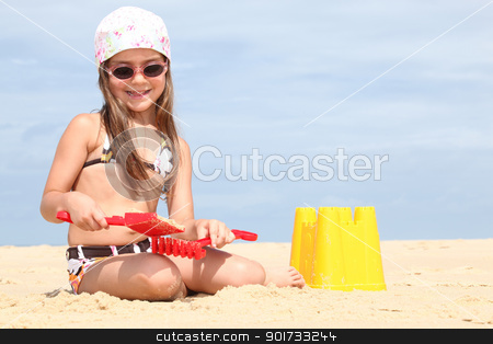Young girl making sandcastles on a beach stock photo, Young girl making sandcastles on a beach by photography33