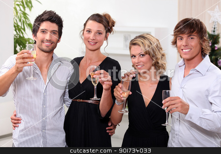 four people toasting in front of a Christmas tree stock photo, four people toasting in front of a Christmas tree by photography33