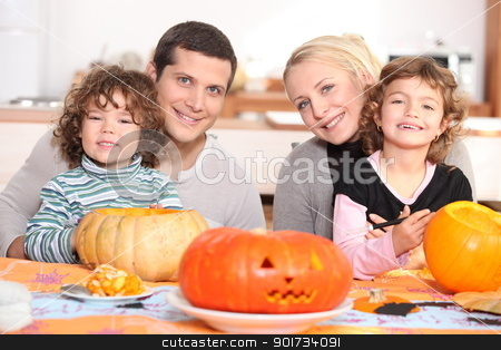 Young family carving pumpkins stock photo, Young family carving pumpkins by photography33