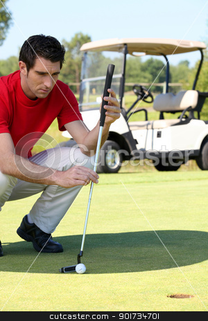 Golfer crouched next to the hole stock photo, Golfer crouched next to the hole by photography33