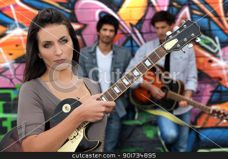 Female guitarist standing with band members in front of a graffitied wall stock photo, Female guitarist standing with band members in front of a graffitied wall by photography33