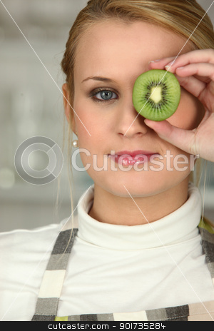 Woman stood with slice of kiwi covering eye stock photo, Woman stood with slice of kiwi covering eye by photography33
