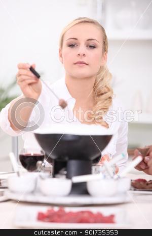 Woman eating steak fondue stock photo, Woman eating steak fondue by photography33