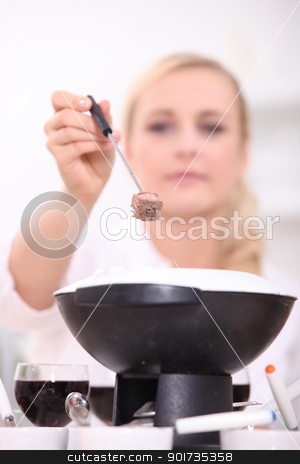 Woman eating a fondue bourguignonne stock photo, Woman eating a fondue bourguignonne by photography33