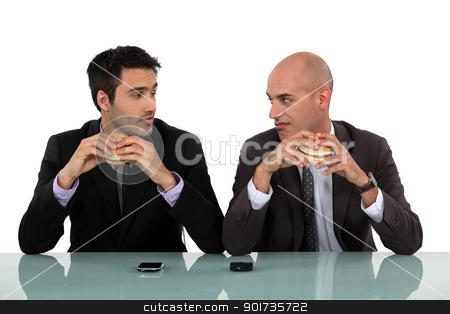 duo of businessmen eating hamburger stock photo, duo of businessmen eating hamburger by photography33