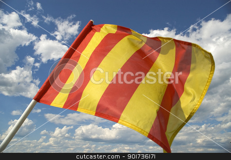 The orange striped flag is yellow. stock photo, The orange striped flag on a background of the dark blue sky with clouds is yellow. by Yury Ponomarev