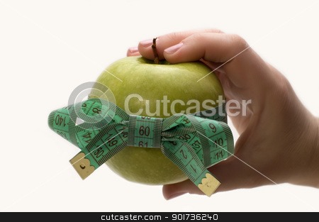 Symbol of diet and healthy eating. stock photo, Green apple with measuring tape in a hand. by Yury Ponomarev