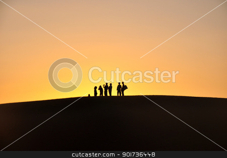 Silhouette of travelers at sunset stock photo, Silhouette of travelers on the top of hills at sunset by John Young