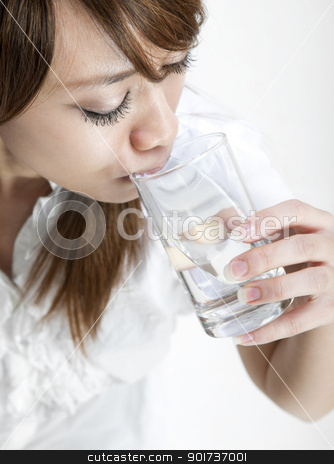 Drinking Water stock photo, Young girl drinking a glass of mineral water by szefei