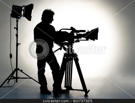TV the camera in studio. stock photo, Searchlight and silhouette of the camera and cameraman. by Yury Ponomarev