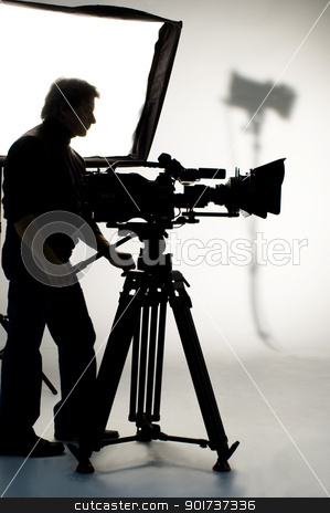 Studio light on location for movie scene. stock photo, Searchlight and silhouette of the camera and cameraman. by Yury Ponomarev