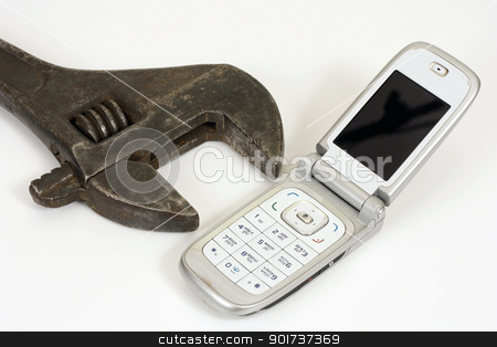 Spanner and telephone. stock photo, Old spanner and modern telephone. by Yury Ponomarev