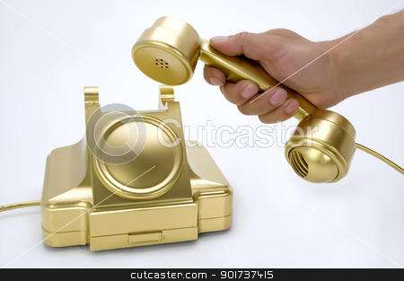 The telephone of gold colour in a hand. stock photo, The telephone of gold colour in a hand on a white background. by Yury Ponomarev