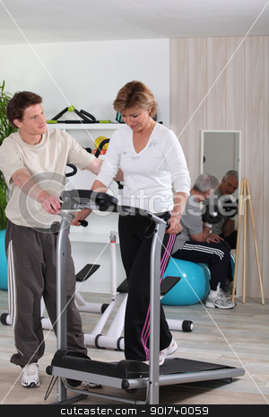 Mature woman using a treadmill stock photo, Mature woman using a treadmill by photography33