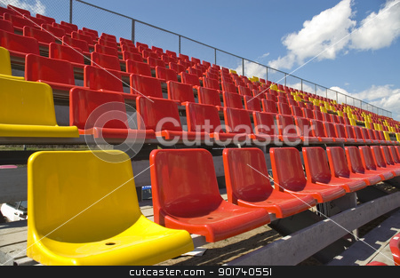 Lines of color seats. stock photo, Red and yellow seats on a background of the sky with clouds. by Yury Ponomarev