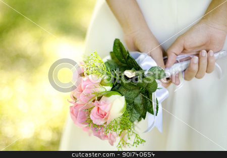 Bridal Bouquet stock photo, Bride holding her bouquet behind her back by szefei