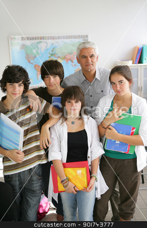 Teenagers standing with their teacher in a classroom stock photo, Teenagers standing with their teacher in a classroom by photography33