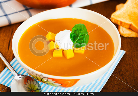 Pumpkin soup with cream in a bowl with painted flower and toast  stock photo, Pumpkin soup with cream in a bowl with painted flower and toast as a garnish on wood table by p.studio66