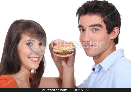 Studio shot of a young couple sharing a hamburger stock photo, Studio shot of a young couple sharing a hamburger by photography33