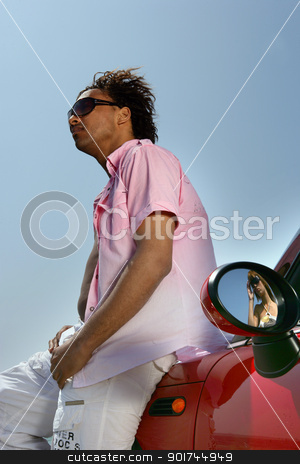 Young man leaning on a convertible car stock photo, Young man leaning on a convertible car by photography33