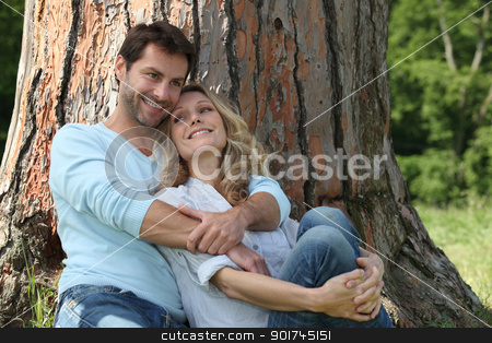Couple sitting against a tree stock photo, Couple sitting against a tree by photography33
