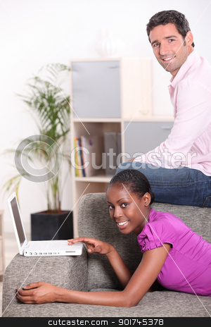 Couple in their lounge with a laptop computer stock photo, Couple in their lounge with a laptop computer by photography33
