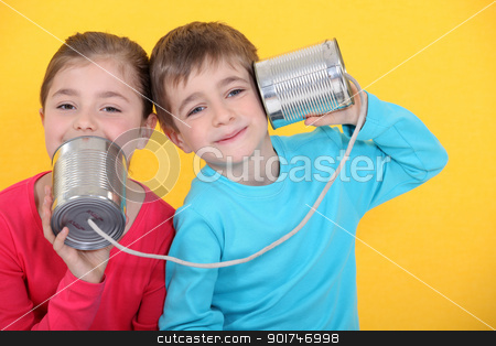 Kids having a phone call with tin cans on yellow background stock photo, Kids having a phone call with tin cans on yellow background by photography33